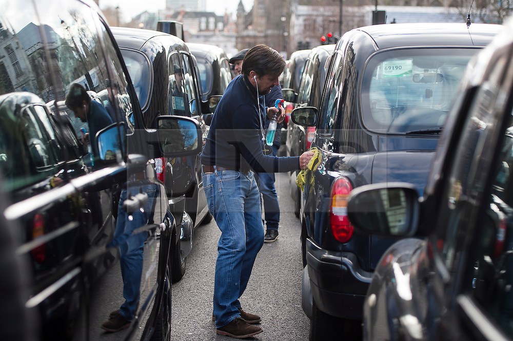© Licensed to London News Pictures. 10/02/2016. London, UK. A cab driver cleaning his cab as thousands of London black cab drivers stage a protest in Westminster, London against Government interference in the taxi industry and 'active support' for Uber, which they allege is a 'tax avoiding global corporation' Photo credit: Ben Cawthra/LNP