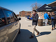 """20 MARCH 2020 - DES MOINES, IOWA: A worker at the Foundry, a distillery in Des Moines, brings hand sanitizer to people waiting in a car. The distillery suspended its distilling operations to make hand sanitizer this week. They distributed it free to people who came to their building. On Friday thousands of people came to get some. There line was more than one mile long. On Friday morning, 20 March, Iowa reported 45 confirmed cases of the Coronavirus. Restaurants, bars, movie theaters, places that draw crowds are closed for at least 30 days. There are no """"shelter in place"""" orders in effect anywhere in Iowa but people are being encouraged to practice """"social distancing"""" and many businesses are requiring or encouraging employees to telecommute.       PHOTO BY JACK KURTZ"""