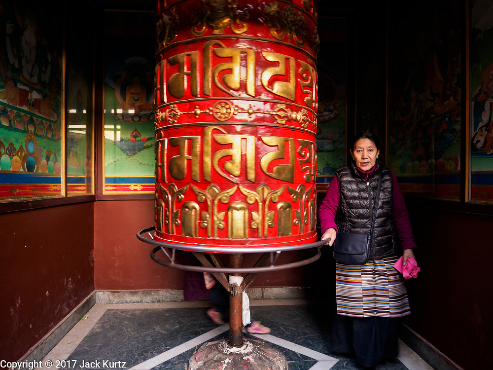 12 MARCH 2017 - KATHMANDU, NEPAL: A Tibetan Buddhist woman prays around a prayer wheel at a monastery at Boudhanath Stupa. Boudhanath Stupa in the Bouda section of Kathmandu is one of the most revered and oldest Buddhist stupas in Nepal. The area has emerged as the center of the Tibetan refugee community in Kathmandu. On full moon nights thousands of Nepali and Tibetan Buddhists come to the stupa and participate in processions around the stupa. The stupa was heavily damaged in the earthquake of 25 April 2015 but has been repaired with the financial assistance of global Buddhist organizations.       PHOTO BY JACK KURTZ