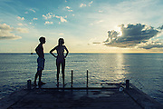 Editorial Travel Photography: Teens enjoying the sunset in Anse d'Arlet, Martinique, caribbean island, Lesser Antilles, France