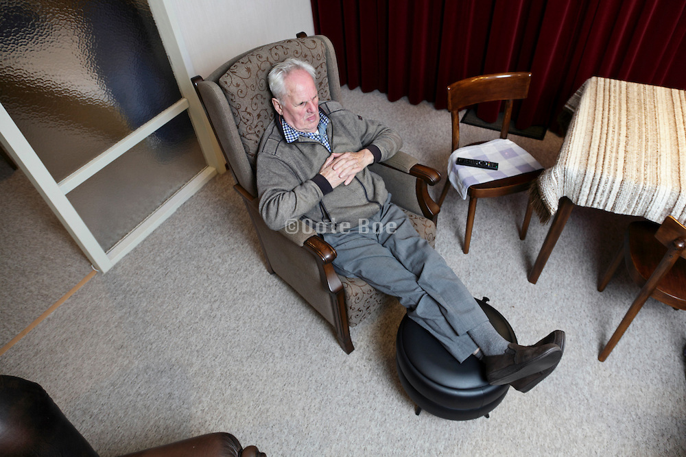 elderly man relaxed in armchair watching television