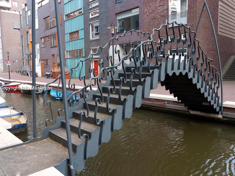 Modern ornate steel footbridge crossing canal in new Java Island housing development in Amsterdam The Netherlands