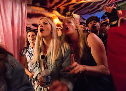© Licensed to London News Pictures. 27/06/2015. Pilton, UK.  Night-time festival atmosphere at Glastonbury Festival 2015 in the Shangri-La area of the festival - festival goers watch another on stage who strips to his underwear at the Kamikaze Karaoke bar, egged on by a male performer in drag with fake breasts.  On Saturday Day 4 of the festival.  Shangri-La is a destroyed dystopian pleasure city.  This years headline acts include Kanye West, The Who and Florence and the Machine, the latter being upgraded in the bill to replace original headline act Foo Fighters. Photo credit: Richard Isaac/LNP