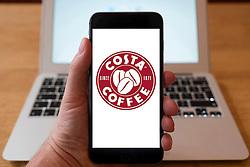 Using iPhone smartphone to display logo of Costa Coffee ,coffee shop chain