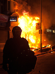 © Licensed to London News Pictures.  FILE PICTURE DATED 09/08/2011 LONDON, UK. A police officer stands in front of a blazing shop on London Road in Croydon after it was set alight by looters.  Croydon was one of several London boroughs and English cities hit by a third night of rioting and looting. Photo credit: Matt Cetti-Roberts/LNP