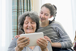 Senior woman with granddaughter using digital tablet at rest home