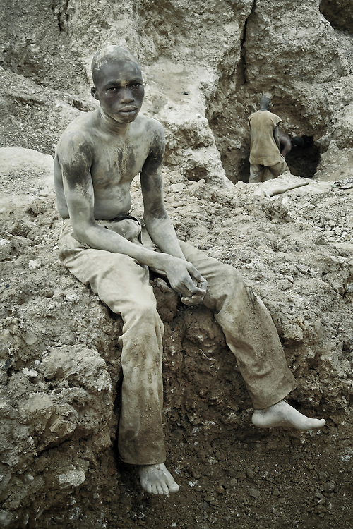Portrait of an African gold miner in Burkina Faso, exhausted and covered in mud from a day down the shaft digging for ore.