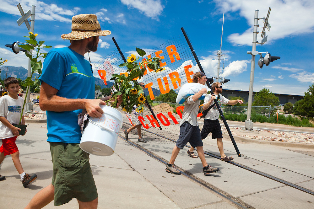 Activists walk up to plant sunflowers in front of the coal-fired Valmont Power Plant in Boulder, Colorado to protest its continued operation. The all-ages group reached the site by riding bicycles from downtown.