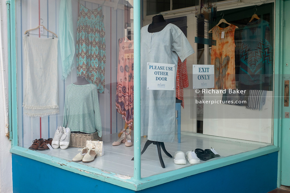 A high street charity shop selling ladies' fashion styles in the window, shows customers the one-way system owners have introduced as shops are re-opening after months of Coronavirus pandemic lockdown, on 19th July 2020, in Whitstable, Kent, England.