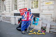 Anti-Brexit protester Steve Bray tidies up around a memorial that offers RIP to democracy with inflatable yellow hammers outside the Cabinet Office in Westminster on 17th September 2019 in London, England, United Kingdom.