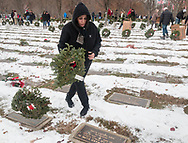 Goshen, New York - A woman gets ready to place a wreath at a grave during a Wreaths Across America ceremony at Orange County Veterans Memorial Cemetery on Dec. 16, 2017. About 3,000 wreaths were placed at graves, and small American flags were added to the wreaths at veterans' graves.