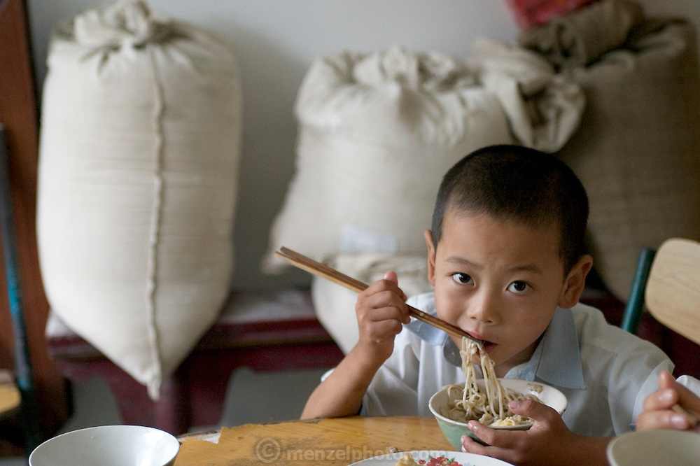 (MODEL RELEASED IMAGE). Cui Yuqi, 6, eats breakfast at the Cuis'. Today breakfast includes fresh eggs from the family hens and hot mian tiao (noodles) with a little cooked spinach and MSG. (Supporting image from the project Hungry Planet: What the World Eats.)