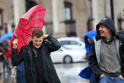 © Licensed to London News Pictures. 15/02/2020. London, UK. A man struggles to control his umbrella in Trafalgar Square during wet and windy weather as Storm Dennis arrives in London. Heavy rain and strong winds are forecast from today until Monday 17 February as the Storm Dennis sweeps across the UK with heavy rain, gale force winds and flooding. Photo credit: Dinendra Haria/LNP