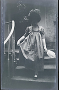 positive of under exposed negative of adult woman coming down the stairs 1920s
