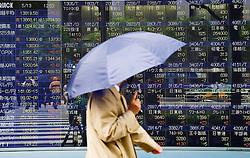 Man walking past electronic stock market price information display screen on a street in Tokyo Japan