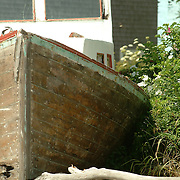 An old lobster boat sits up on the shore far from the water in Stonington, Maine,