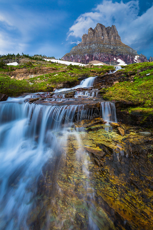 "Glacier National Park is a national park located in the U.S. state of Montana, on the Canada–United States border with the Canadian provinces of Alberta and British Columbia. The park encompasses over 1 million acres and includes parts of two mountain ranges (sub-ranges of the Rocky Mountains), over 130 named lakes, more than 1,000 different species of plants, and hundreds of species of animals. This vast pristine ecosystem is the centerpiece of what has been referred to as the ""Crown of the Continent Ecosystem"", a region of protected land encompassing 16,000 square miles.<br /> <br /> The region that became Glacier National Park was first inhabited by Native Americans. Upon the arrival of European explorers, it was dominated by the Blackfeet in the east and the Flathead in the western regions. Soon after the establishment of the park on May 11, 1910, a number of hotels and chalets were constructed by the Great Northern Railway. These historic hotels and chalets are listed as National Historic Landmarks and a total of 350 locations are on the National Register of Historic Places. By 1932 work was completed on the Going-to-the-Sun Road, later designated a National Historic Civil Engineering Landmark, which provided greater accessibility for automobiles into the heart of the park.<br /> <br /> The mountains of Glacier National Park began forming 170 million years ago when ancient rocks were forced eastward up and over much younger rock strata. Known as the Lewis Overthrust, these sedimentary rocks are considered to have some of the finest fossilized examples of extremely early life found anywhere on Earth. The current shapes of the Lewis and Livingston mountain ranges and positioning and size of the lakes show the telltale evidence of massive glacial action, which carved U-shaped valleys and left behind moraines which impounded water, creating lakes. Of the estimated 150 glaciers which existed in the park in the mid-19th century, only 25 active glaciers remained by 2010. Scientists studyin"