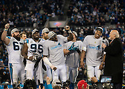 """CHARLOTTE, NC - JAN 24:  Members of the Carolina Panthers lead an """"MVP"""" chant for quarterback Cam Newton #1 during his interview with Fox Sports analyst Terry Bradshaw after the NFC Championship game against the Arizona Cardinals at Bank of America Stadium on January 24, 2016 in Charlotte, North Carolina."""