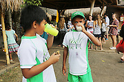 """Boys wearing Green School sports wear<br /><br />The Green School (Bali) is one of a kind in Indonesia. It is a private, kindergarten to secondary International school located along the Ayung River near Ubud, Bali, Indonesia. The school buildings are of ecologically-sustainable design made primarily of bamboo, also using local grass and mud walls. There are over 600 students coming from over 40 countries with a percentage of scholarships for local Indonesian students.<br /><br />The impressive three-domed """"Heart of School Building"""" is 60 metres long and uses 2500 bamboo poles. The school also utilizes renewable building materials for some of its other needs, and almost everything, even the desks, chairs, some of the clothes and football goal posts are made of bamboo.<br /><br />The educational focus is on ecological sustainability. Subjects taught include English, mathematics and science, including ecology, the environment and sustainability, as well as the creative arts, global perspectives and environmental management. This educational establishment is unlike other international schools in Indonesia. <br /><br />Renewable energy sources, including solar power and hydroelectric vortex, provide over 50% of the energy needs of the school. The school has an organic permaculture system and prepares students to become stewards of the environment. <br /><br />The school was founded by John and Cynthia Hardy in 2008."""