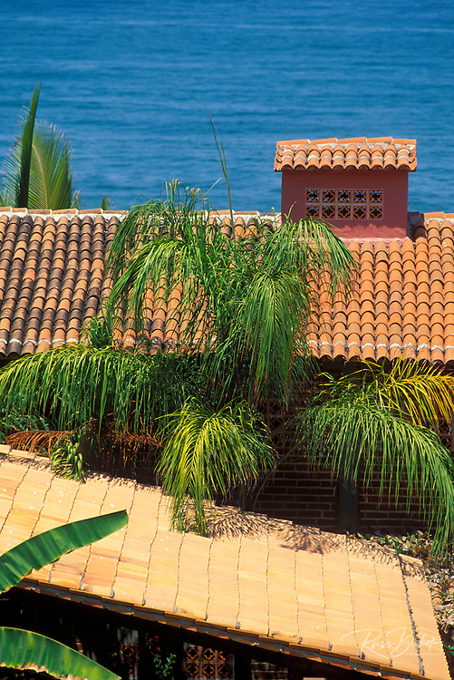 Spanish tile roof and palms above the blue Pacific Ocean in Sayulita, Nayarit, Mexico