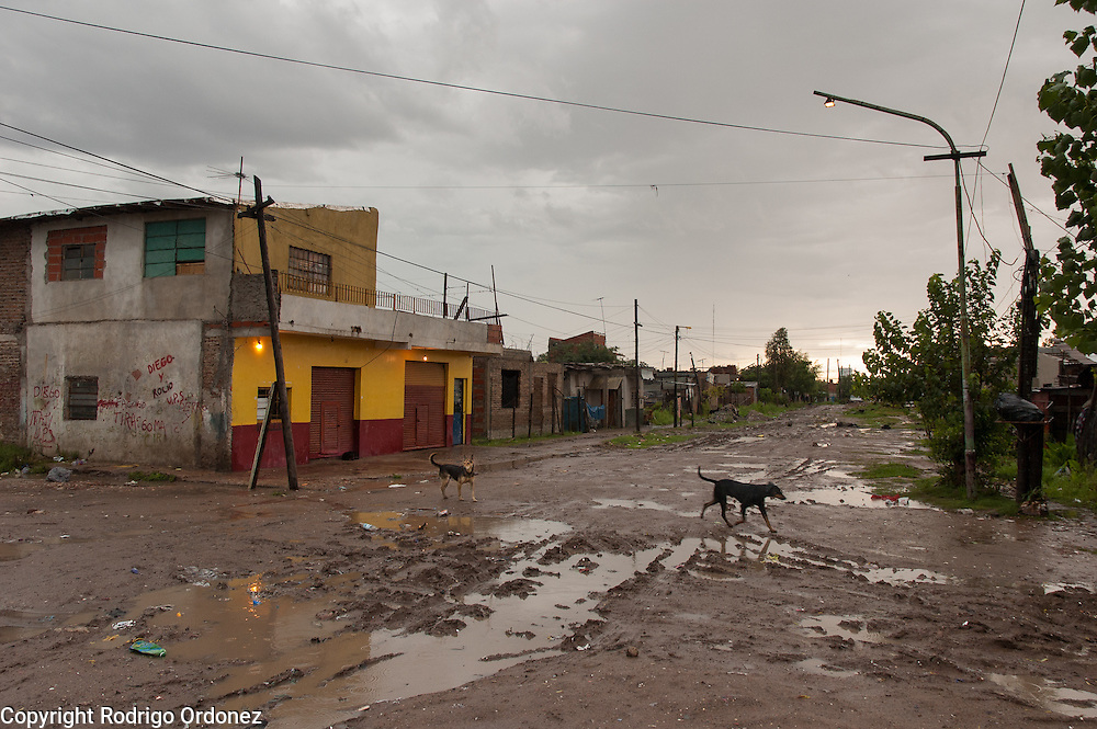General view of one of the main streets of Ocho de Mayo, an informal settlement in the district of General Saint Martín, Buenos Aires, Argentina, in January 2006. The neighborhood is named after the date in which the first settlers moved in, on the 8th of May of 1998. <br /> Today, Ocho de Mayo is home to about 1,500 families, many of them young. Of the 5,000 residents, 3,000 are under 16. About 65 percent of the population is Paraguayan. The rest are from nearby towns or elsewhere in Argentina. This neighborhood does not look very different from the villas miseria —slums or shantytowns— that ring the Argentine capital.