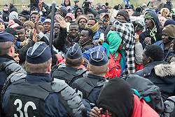 © Licensed to London News Pictures . 24/10/2016 . Calais , France . A fight breaks out close to the front of the queue as people crush together and push forward . Migrant campers are evicted from the Jungle migrant camp in Calais , Northern France , on the day of a planned eviction and start of the destruction of the camp . Photo credit: Joel Goodman/LNP
