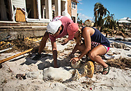 Family members of Thomas L Wood recover a broken mermaid in the sand in the back of the  Driftwood Inn in  Mexico Beach, Florida that was badly damaged by Hurricane Michael.