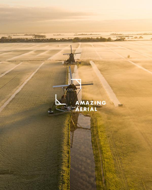 Aerial view of windmills in morning fog during sunrise in Aarlanderveen, Alphen aan den Rijn, Netherlands.