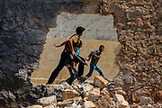 Members of the Free Syrian Army are seen rushing to take cover in Anadan following a government airstrike. The city resembled a ghost town on Monday, June 25, 2012. It bears the scars from Syrian President Bashar al-Assad's use of military force to crush an opposition movement that has spawned an armed insurgency against his rule. (Photo by Vudi Xhymshiti)