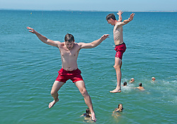 © Licensed to London News Pictures 22/07/2021. Whitstable, UK. Young men having fun jumping off the Harbour Arm in Whitstable. Another hot heatwave day as people enjoy a day out at Whitstable in Kent. Photo credit:Grant Falvey/LNP