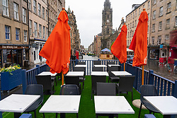 Scotland, Scotland, UK. 24 May 2021. Unseasonable cool and damp weather in Edinburgh meant that there were few customers in the many outdoor bars , cafes and restaurants in the city centre, With few tourists in the capital the streets remain much quieter than normal. Pic; Outdoor seating for bars and restaurants lie empty at lunchtime on the Royal Mile. Iain Masterton/Alamy Live News