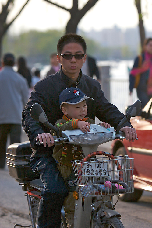 A man and child ride by the Houhai lake on an electric bike in the  Shichahai area in Beijing,China.