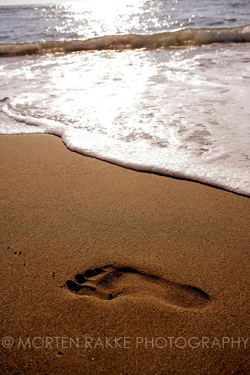 Footprints in sand at beach, Italy