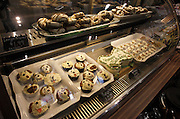"""A view inside the display case of Whisker Bones shows doggie donuts, a birthday cake shaped like a bone, cookies, and """"pupcakes""""."""