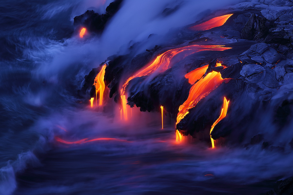 Glowing bits of lava are pulled seaward by the receding surf in the mesmerizing interaction of molten rock and the cool Pacific. A display of pahoehoe dripping into the sea at the Kamokuna ocean entry creates the newest land on the planet.