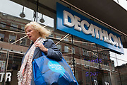 A woman with a blue shopping bag passes by a city centre branch of the high street sportswear chain Decathlon on 2nd September, 2021 in Leeds, United Kingdom. Decathlon is a French sporting goods retailer with branches all over the world.