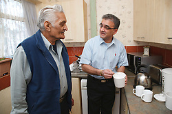Elderly south Asian father and son in kitchen.