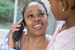 Woman on the phone while her young daughter listens in,