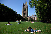 Houses of Parliament from The Victoria Tower Gardens, Westminter, London. People enjoy laying in the sun on the grass.