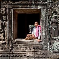 Buddhist nun sitting in a window frame in Banteay Kdei.