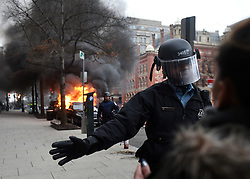 January 20, 2017 - Washington, DC, U.S - Police in riot gear hold back the crowd of protesters after a limousine was set on fire during clashes on President Donald Trump's inauguration day in Washington, D.C., on Jan. 20, 2017. (Credit Image: © Carol Guzy via ZUMA Wire)