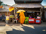 """15 FEBRUARY 2019 - SIHANOUKVILLE, CAMBODIA: A Buddhist monk collects alms at a small convenience shop a migrant camp in Sihanoukville during his morning alms rounds. Families who live in the shanty town came to Sihanoukville from other Cambodian provinces because of the town's booming economy and construction industry building Chinese resorts and casinos. There are about 80 Chinese casinos and resort hotels open in Sihanoukville and dozens more under construction. The casinos are changing the city, once a sleepy port on Southeast Asia's """"backpacker trail"""" into a booming city. The change is coming with a cost though. Many Cambodian residents of Sihanoukville  have lost their homes to make way for the casinos and the jobs are going to Chinese workers, brought in to build casinos and work in the casinos.     PHOTO BY JACK KURTZ"""