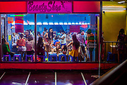 """12 JANUARY 2013 - BANGKOK, THAILAND:  Workers in the Nana Entertainment Plaza in Bangkok get their hair and makeup done before going to work in the go-go bars and brothels in the district. Prostitution in Thailand is illegal, although in practice it is tolerated and partly regulated. Prostitution is practiced openly throughout the country. The number of prostitutes is difficult to determine, estimates vary widely. Since the Vietnam War, Thailand has gained international notoriety among travelers from many countries as a sex tourism destination. One estimate published in 2003 placed the trade at US$ 4.3 billion per year or about three percent of the Thai economy. It has been suggested that at least 10% of tourist dollars may be spent on the sex trade. According to a 2001 report by the World Health Organisation: """"There are between 150,000 and 200,000 sex workers (in Thailand).""""    PHOTO BY JACK KURTZ"""