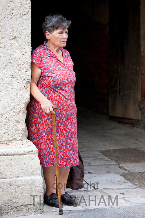 Local woman watches Contrada parade in Asciano, inTuscany, Italy