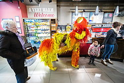 © Licensed to London News Pictures . 09/02/2019. Manchester , UK . Two men dressed as a lion queue in a branch of Costa Coffee , after performing a lion dance on Market Street in Manchester City Centre during Chinese New Year Celebrations in the city . Photo credit : Joel Goodman/LNP