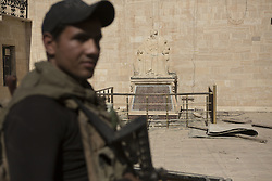October 23, 2016 - Bartella, Nineveh, Iraq - An Iraqi Army Counter Terrorism trooper stands guard near a statue defaced by Islamic State militants at the Mart Shmony Church, in Bartella, Iraq...Bartella, a mainly Christian town with a population of around 30,000 people before being taken by the Islamic State in August 2014, was captured two days ago by the Iraqi Army's Counter Terrorism force as part of the ongoing offensive to retake Mosul. Although ISIS militants were pushed back a large amount of improvised explosive devices are still being found in the town's buildings. (Credit Image: © Matt Cetti-Roberts/London News Pictures via ZUMA Wire)