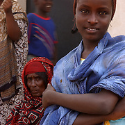 A woman of Alaili Dadda poses for the camera while U.S. military troops ask questions of the village elders. In order to make this picture the photographer befriended a young man who asked the woman if the photographer could make the picture. She agreed, and looked at the camera. This was uncommon.  Djiboutian women are very  shy and deferent to men in most cases. It is considered rude to look at women and speaking to them is also considered inappropriate. <br /> U.S. Military service members visited Alaili Dadda, a village of 300 near Obok, Djibouti to assess the diffuculty of drilling a well in here. The long term goal is to provide running water to several local clinics.  U.S. Navy Photo by Mass Communication Specialist 2nd Class Roger S. Duncan. (RELEASED)