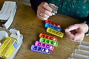 Nederland, Nijmegen, 16-9-2014 Een vrouw met een auto immuunziekte vult haar pillendoosje met zeven vakjes met medicijnen voor de dagen van de week. Foto: Flip Franssen/Hollandse Hoogte