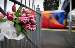 © Licensed to London News Pictures. 05/01/2019. Horsley, UK. A train leaves Horsley station in Surrey past a floral tribute on a gate where a man was stabbed to death on a train yesterday. A murder investigation has been launched after the man was attacked while on board the 12. 58pm train service travelling between Guildford and London Waterloo. A man and a woman have been detained by police in Farnham in connection with the murder. Photo credit: Peter Macdiarmid/LNP