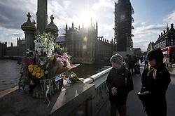 © Licensed to London News Pictures. 22/03/2018. London, UK. Members of the public look at floral tributes on Westminster Bridge in London on the one year anniversary of the Westminster Bridge Terror attack. Lone terrorist, 52-year-old Briton Khalid Masood, killed four people by driving a car at pedestrians then managed to gain entry to the grounds of the Houses of Parliament, killing police officer Keith Palmer. Photo credit: Ben Cawthra/LNP